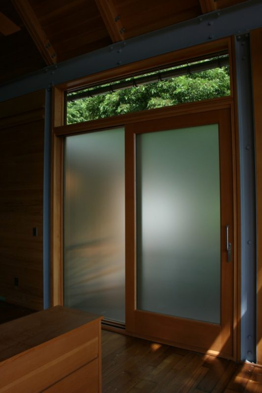 Frosted glass lift slide in master bedroom, framed in steel