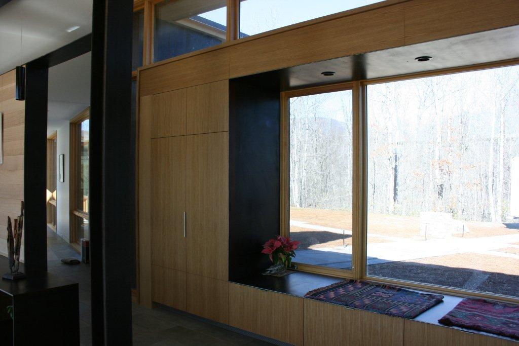 This is a continuation of the kitchen cabinetry incorporating a custom closet and window seat