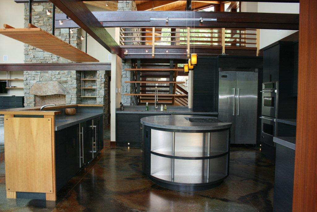Stainless steel shelving and integrated cook top flush with concrete kitchen island.